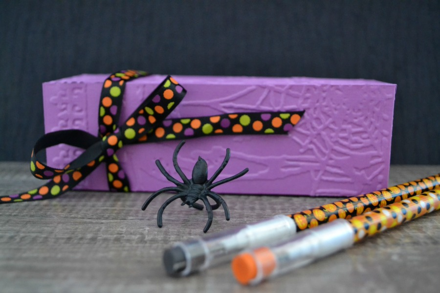 DIY embossed Halloween favor box perfect to fill up with class party favors or to pass out at a Halloween party. Fill with candy, pencils, and plastic rings